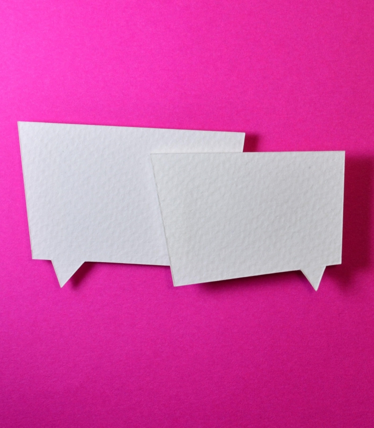 Two overlapping white conversation bubbles on a pink background